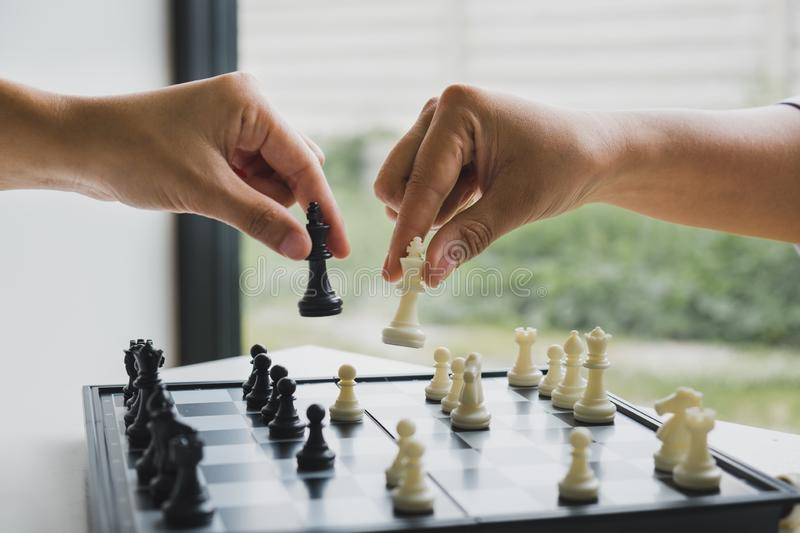 Hand holding chess pieces on board with white background, driven to success Business Strategy.  stock photography