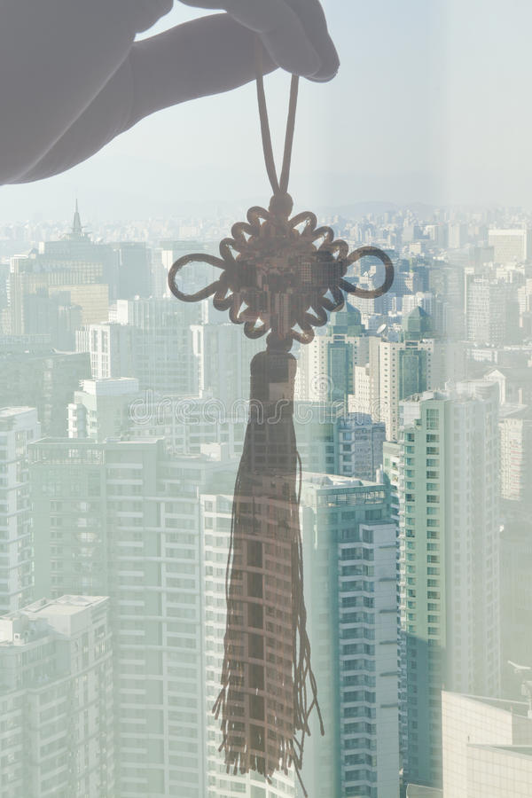 Hand Holding Chinese Knot, Double exposure over the cityscape during the day, Beijing, China stock image