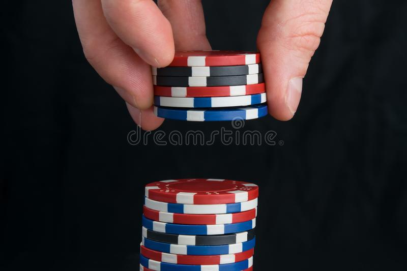 Hand holding chips, for playing in the casino, to increase the rate, on a black background, with reflection stock photos