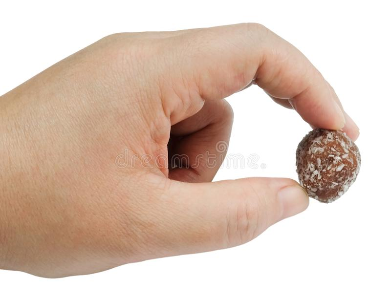 Hand Holding Chocolate Candy Balls with Grate Coconut stock photo