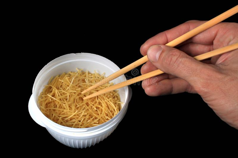 Hand holding chopsticks in a bowl of dry noodles stock photos