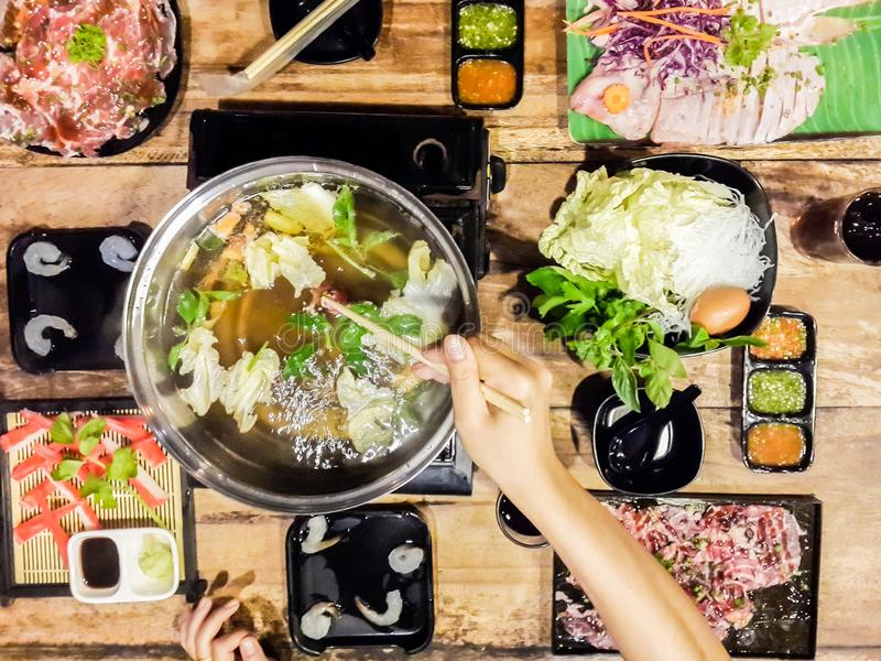 Hand holding chopsticks eating.Sukiyaki and shabu soup with Dumplings, white cabbage, crab, vermicelli, shrimp. And in a white cup on wooden royalty free stock photos