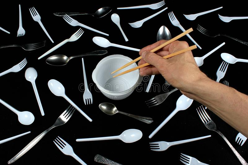 Hand holding chopsticks in empty bowl on black background stock images