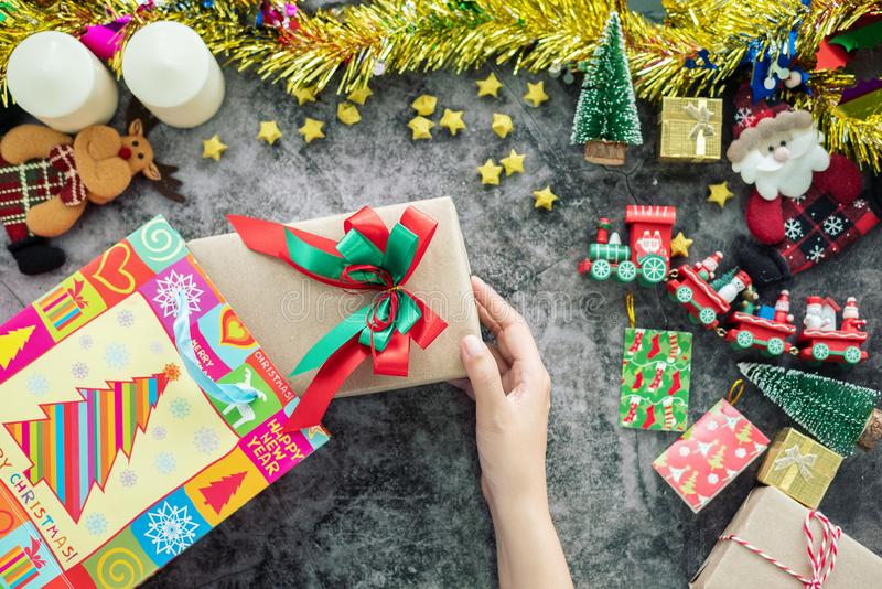 Hand holding Christmas gift box from shopping bag during Christmas season and gift festival, decorations with Christmas ornament stock image