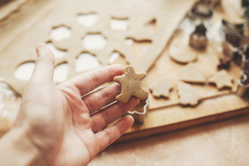 Hand holding christmas gingerbread cookie man on background of w. Ooden rolling pin, cookies, metal cutters, christmas decorations on rustic table. Process of royalty free stock images