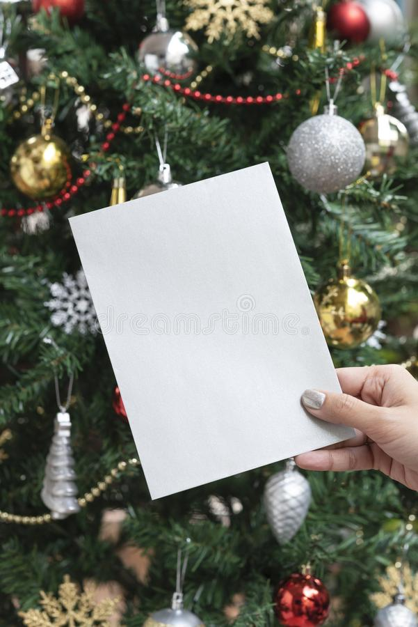 Hand holding christmas holiday greeting design mockup card on christmas tree background stock photos