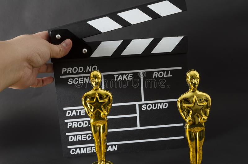 Hand holding a clapboard and two plastic Oscar awards. XALAPA, VERACRUZ, MEXICO- FEBRUARY 14, 2019: Hand holding a clapboard and two plastic Oscar awards against royalty free stock images