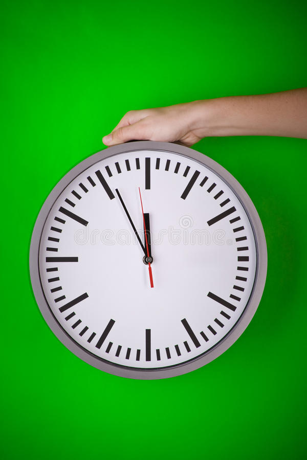 Hand holding a clock. A hand holding a large clock in front of a front wall stock photos