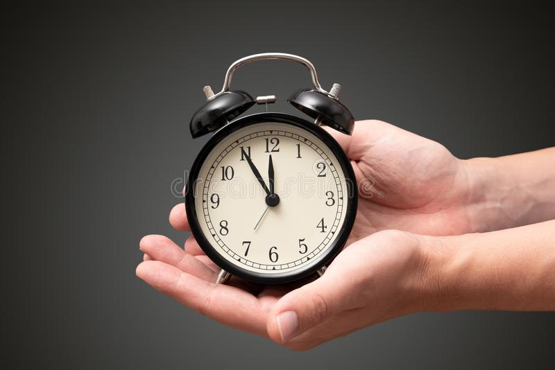 Hand holding clock with five minutes to twelve o`clock royalty free stock photos