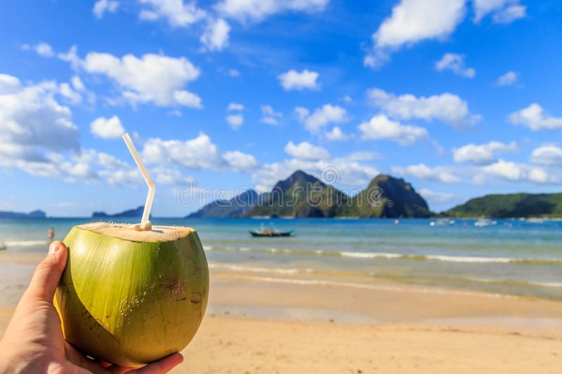 Hand holding a coconut coco loco coctail with straw, tropical islands, beach, sea and blue sky in the background, El Nido, Palawan royalty free stock photos