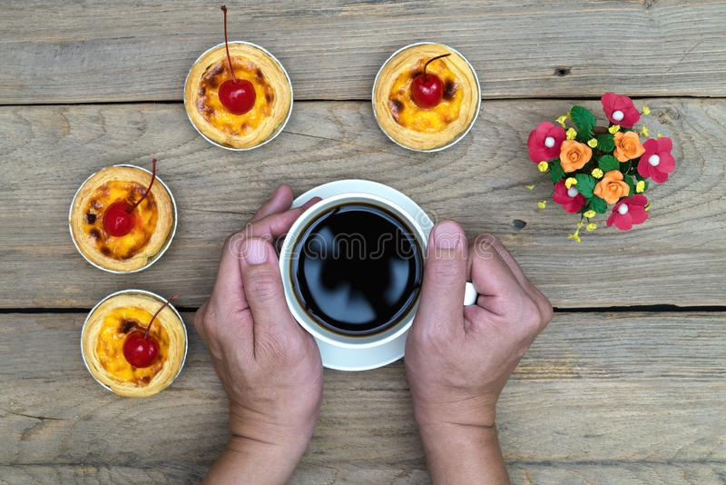 Hand holding coffee cup with egg tart on wood table,top view. Hand holding coffee cup with egg tart on wood table ,top view stock image