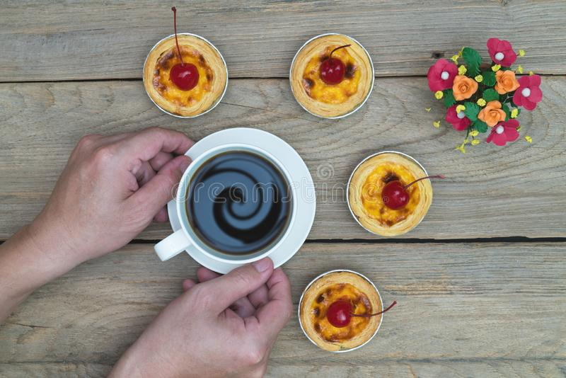 Hand holding coffee cup with egg tart on wood table,top view. Hand holding coffee cup with egg tart on wood table ,top view royalty free stock images