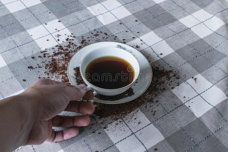 Hand holding coffee cup over spilled coffee beans royalty free stock image