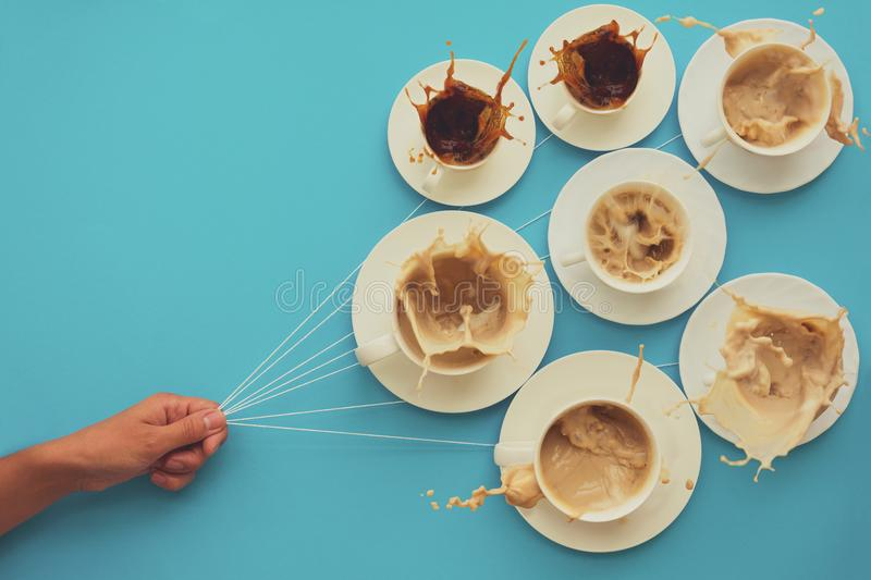 Hand holding coffee cups with milk and without in shape of balloons on blue paper background. Toned. Weather or good morning conce. Pt stock photography
