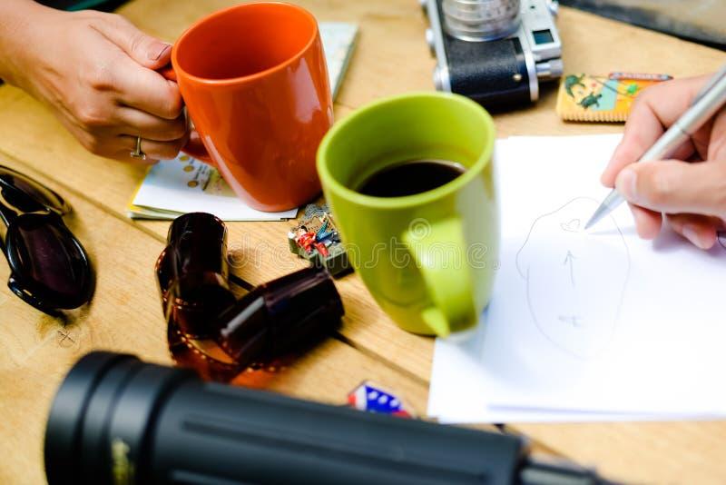 Hand holding coffee mug and sketch writing hand stock images