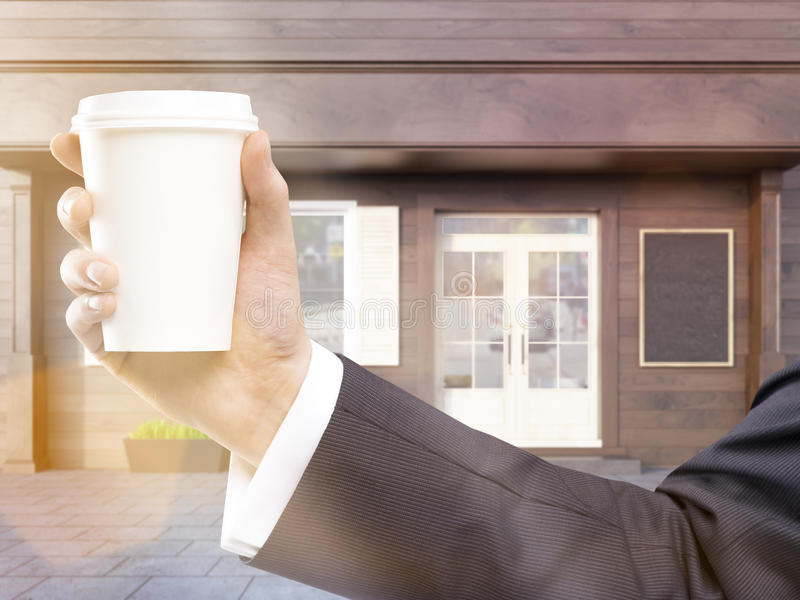 Hand holding coffee toning. Hand holding blank coffee cup on cafe exterior background. Toned image. Mock up, 3D Rendering royalty free illustration