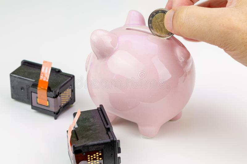 Hand holding a coin next to a piggy bank and two ink cartridges. Cost of ink concept royalty free stock images