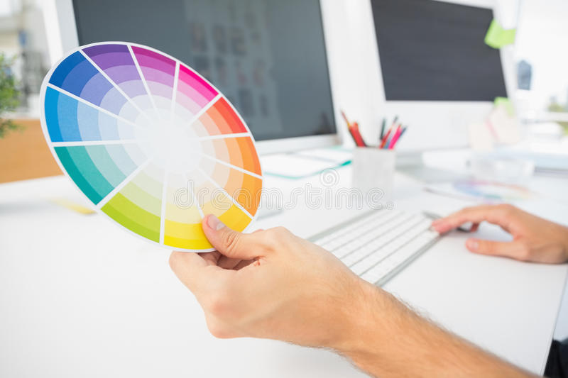 Hand holding color wheel while using computer royalty free stock photo