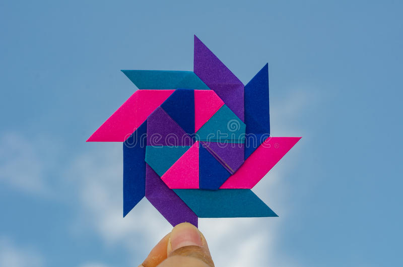 Hand holding colorful weathercock origami folding paper stock photo