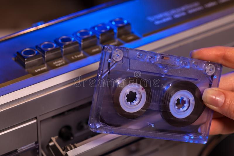 Hand holding compact audio cassette tape - closeup royalty free stock image