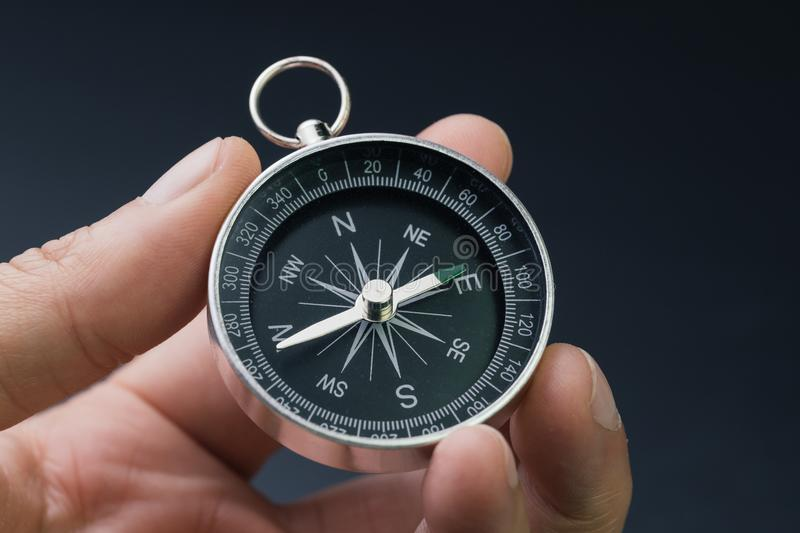 Hand holding compass, business or economy direction, world exploration or decision concept stock photos