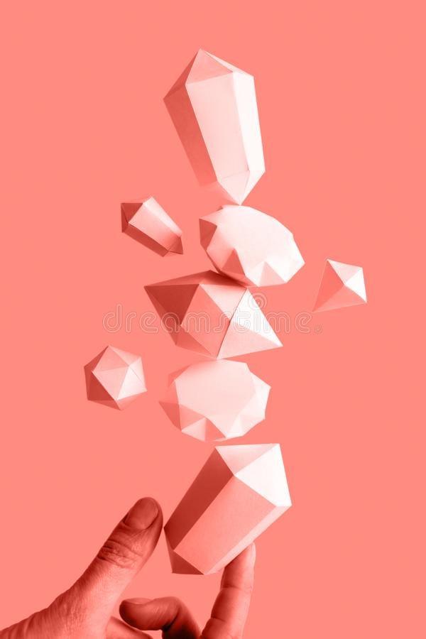 Polygonal diamonds made of paper on a blue background. Hand holding a composition of paper diamonds floating in the air, balance, levitation Toned trendy coral stock image