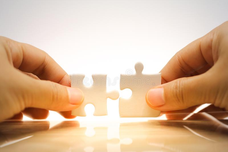 Hand holding and connecting jigsaw puzzles stock image