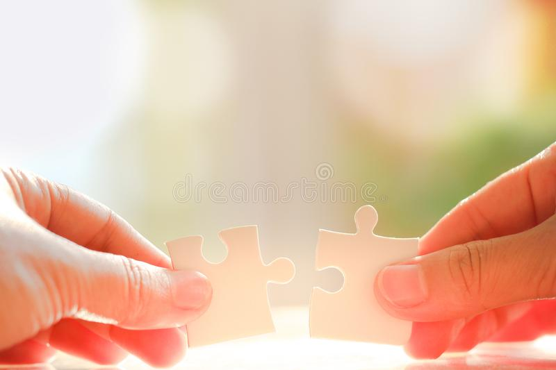 Hand holding and connecting jigsaw puzzles. Woman`s hand holding and connecting jigsaw puzzles. Business solutions, connection, achievement, and strategy concept royalty free stock image