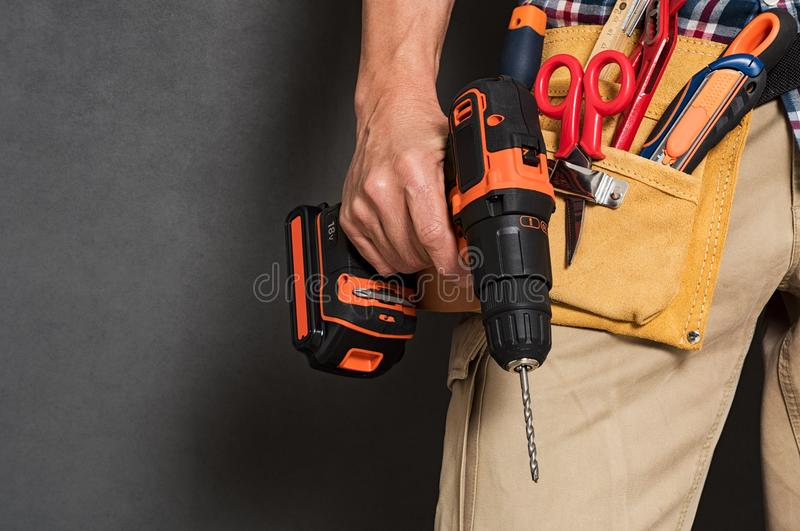 Hand holding construction tools. Close up of handyman holding a drill machine with tool belt around waist. Detail of artisan hand holding electric drill with royalty free stock photo