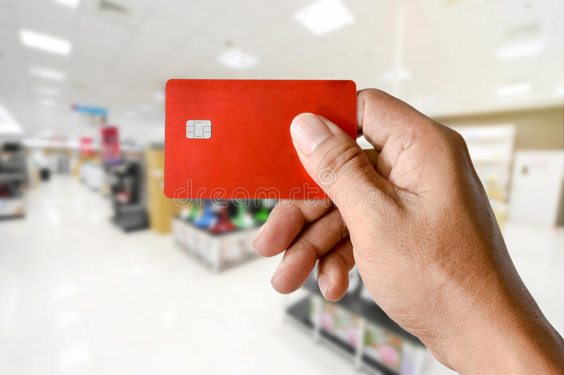 A hand holding credit card on blurred electronics store royalty free stock photo