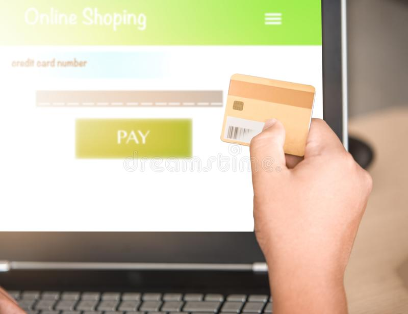 Hand holding credit card with laptop stock image