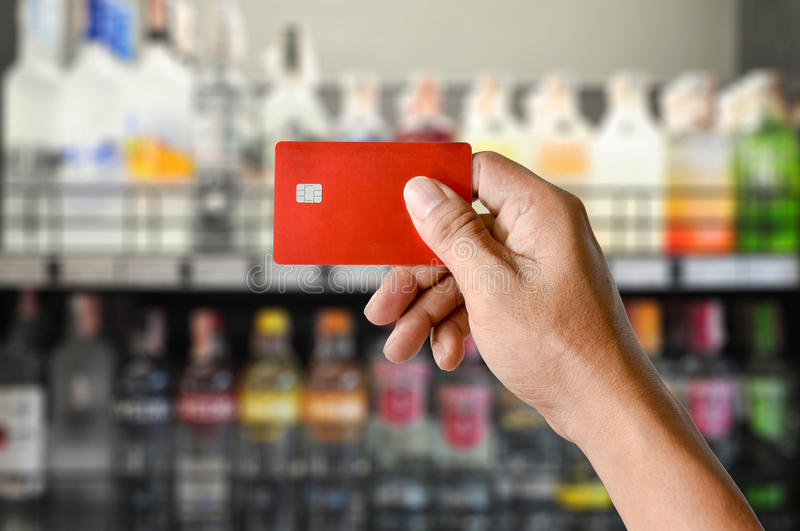 A hand holding credit card on Wine Supermarket store background. A hand holding credit card on Wine Liquor bottle on shelf, Blurred Supermarket store background royalty free stock photography