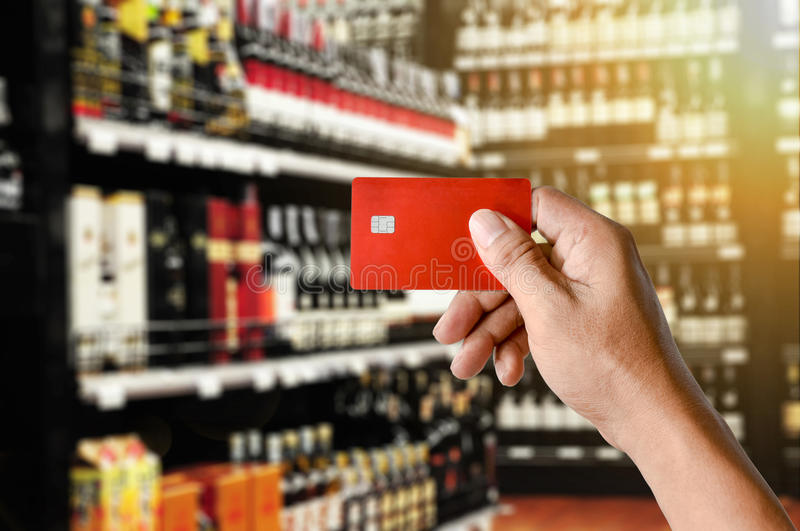 A hand holding credit card on Wine Supermarket store background. A hand holding credit card on Wine Liquor bottle on shelf, Blurred Supermarket store background royalty free stock photos