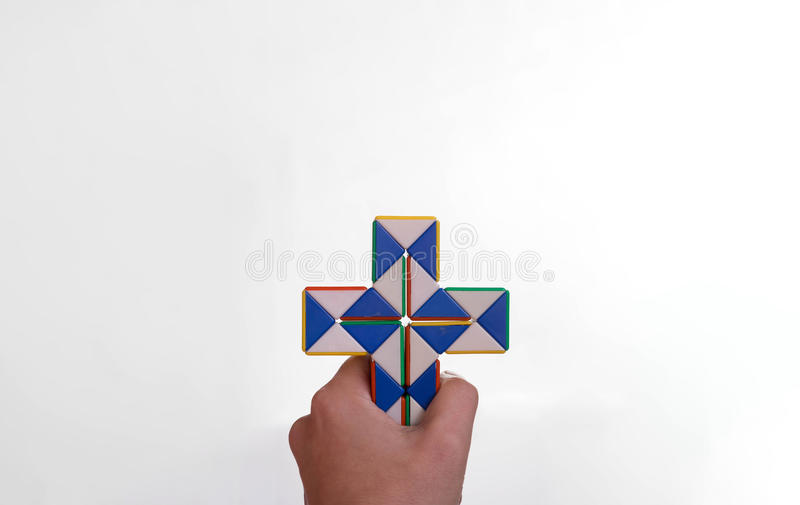 Hand holding a crucifix. Twist toy stock photo