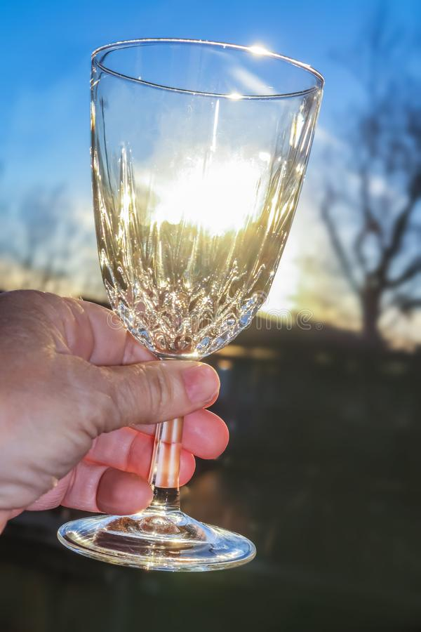 Hand holding a crystal wine glass up and the light shining through it - outdoor shot with blurred winter tree and late afternoon s. Un in background royalty free stock photo