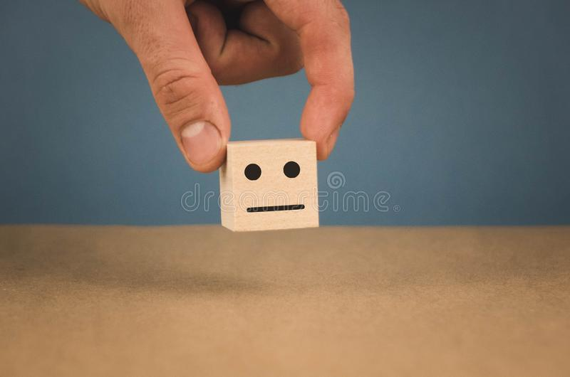 Hand holding a cube with a neutral smiley on a blue background royalty free stock photo