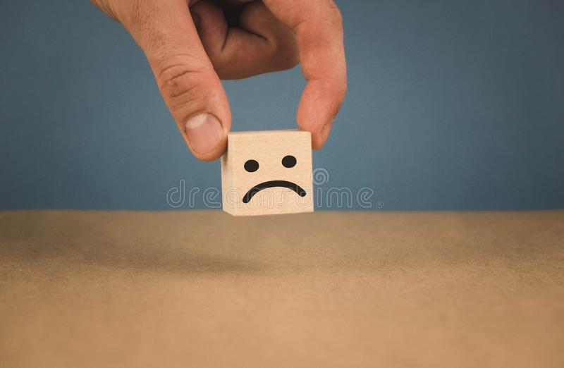 Hand holding a cube with a sad smiley on a blue background stock photos