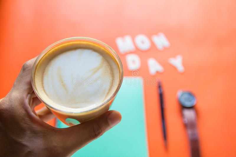 Hand holding cup of Coffee with monday ,wood text minimalist layout  On orange background. Leave blank for your text stock photography