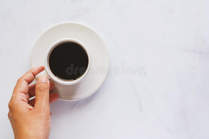 Hand holding cup of coffee with saucer on white marble backgroun royalty free stock images
