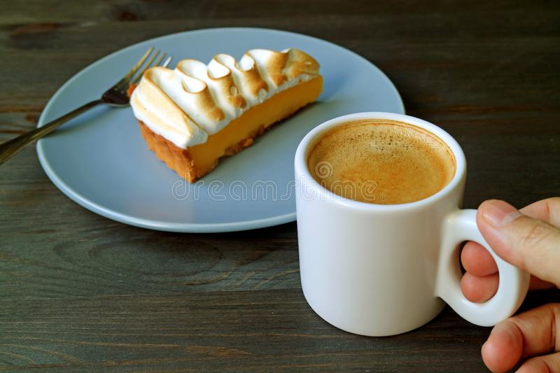 Hand Holding a Cup of Coffee with a Slice of Lemon Meringue Tart in Background. Relaxing time, Take a Break royalty free stock photos