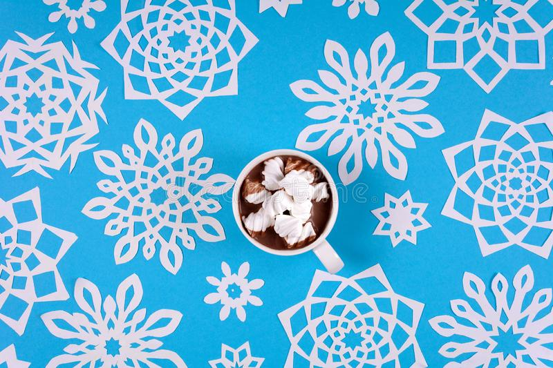 Hand holding cup of hot chocolate with marshmallow and paper snowflakes on blue background. Top view. Christmas decoration stock photography