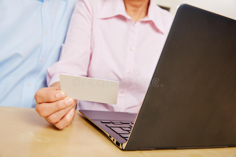 Hand holding customer card while shopping online. Hand holding customer credit card while shopping online with laptop computer stock images