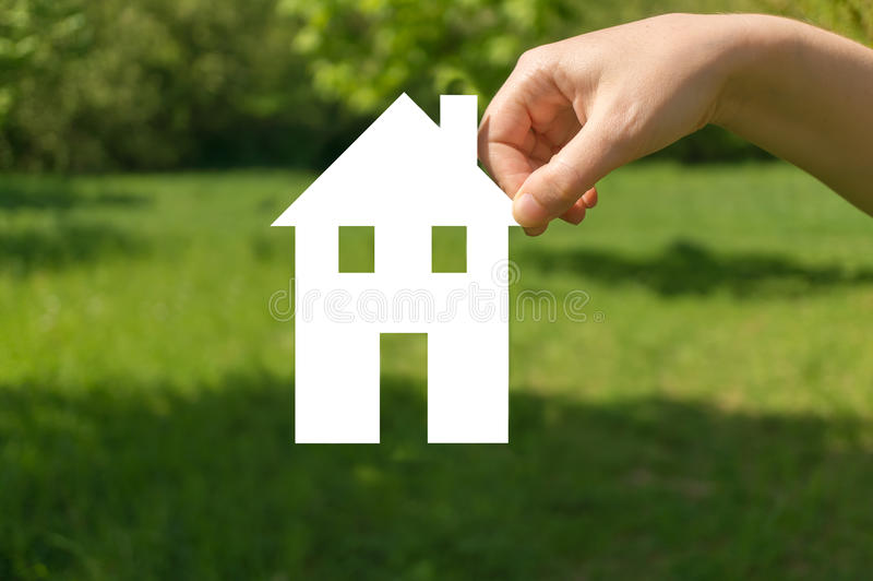 Hand holding cut off paper house as symbol of mortgage. Hand holding cut off white paper house in nature as symbol of mortgage stock photo