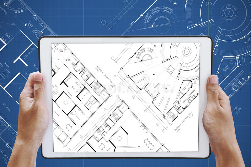 Hand holding digital tablet with architectural planning on screen download hand holding digital tablet with architectural planning on screen and architectural blueprint background stock malvernweather Gallery