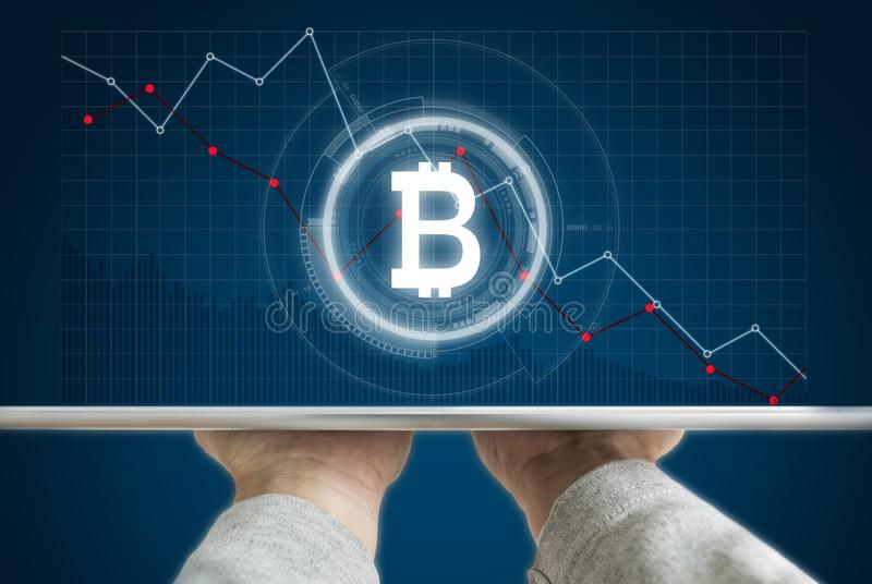 Hand holding digital tablet with B symbol of Bitcoin, internet banking and block chain and decreasing graph background. S royalty free stock image