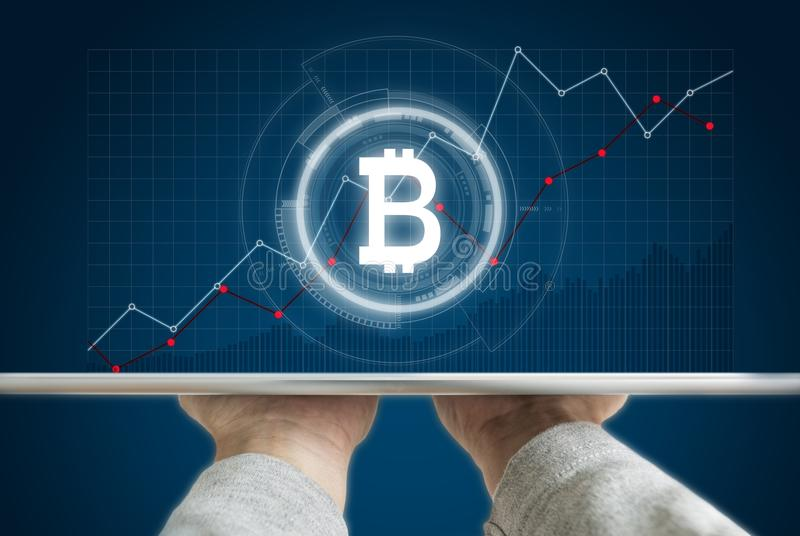 Hand holding digital tablet with B symbol of Bitcoin, internet banking and block chain and raising graph background. S royalty free stock photo