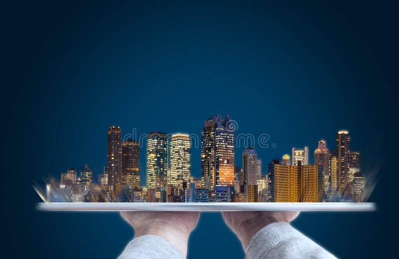 Hand holding digital tablet with modern buildings hologram. Building technology, real estate business and smart city concept. S royalty free stock photo