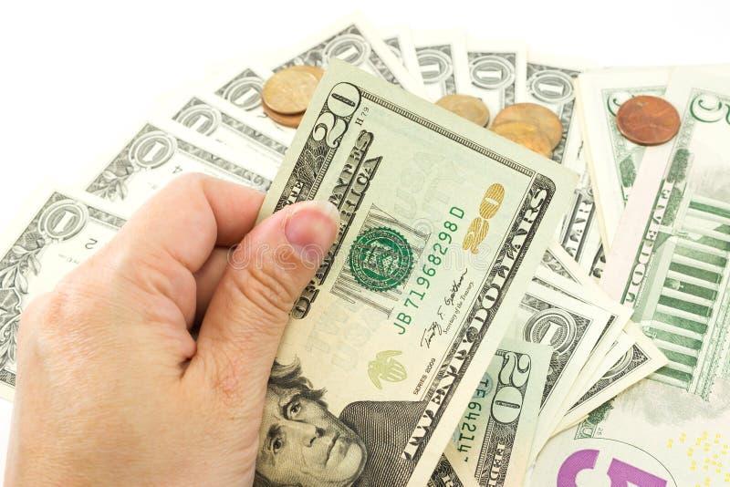 Hand holding dollar bill. Left hand holding dollar bill with coins and dollar bill are background stock photos