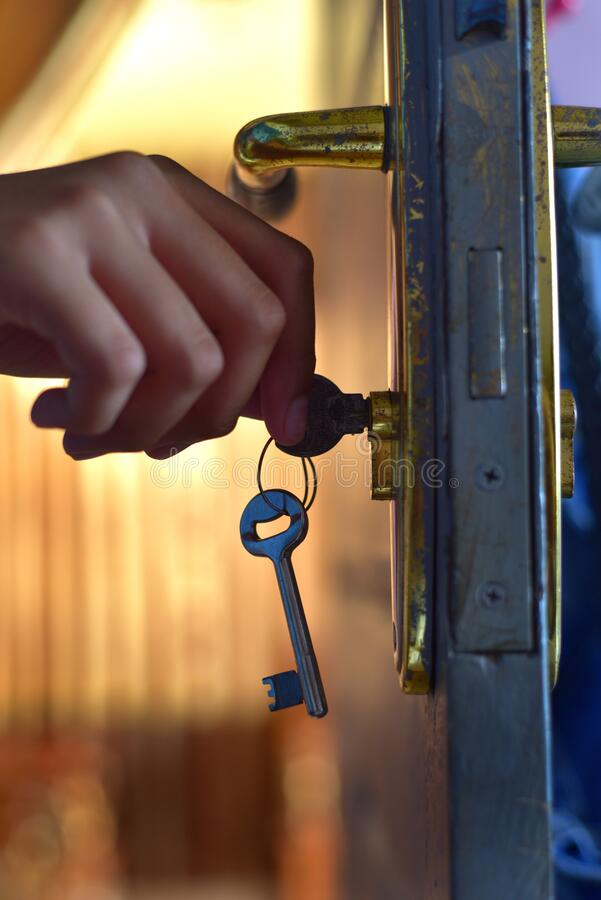 Hand holding on the door key stock images