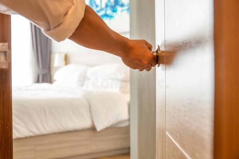 Hand holding door knob of the bedroom selected focus. stock photography